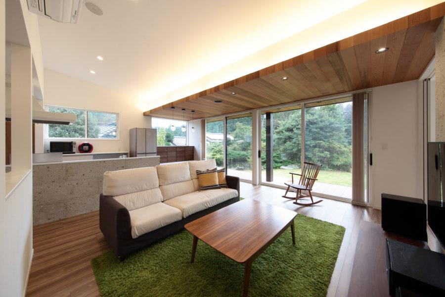 壁を最小限にし、天井まで広がりを持たせた大開口の窓。テレビ後ろの壁面には大谷石を採用。洗練された空間を演出する