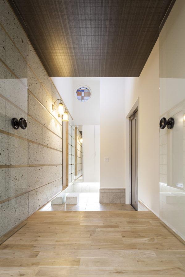 玄関ホールは大谷石やナラ床材、ガラス扉など異素材が響き合う洗練された空間となった