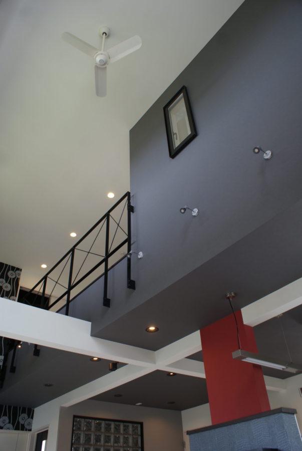 2階廊下部分の一部に壁を設け、デザイン性のある空間に。モノトーンカラーのなかに耐力壁の赤がアクセントになっている