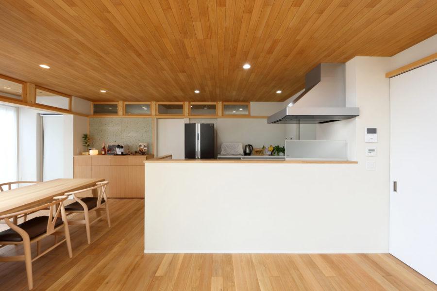 床と天井には無垢のオーク材、壁には漆喰を採用し上質な空間を創出する。キッチン上部にも換気できる欄間を設置。奥の造作家具の壁には表情豊かな大谷石を採用