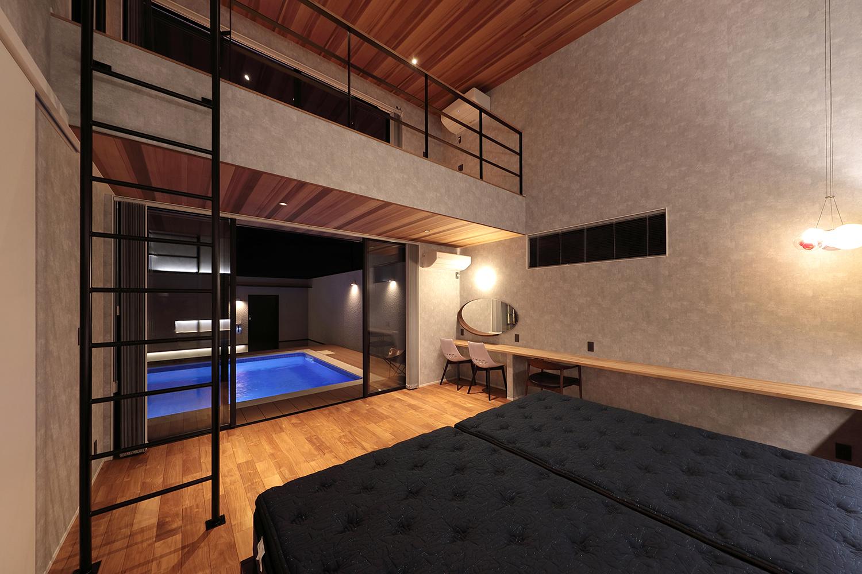 ベッドからもプールを望める優雅な寝室。高い天井に遊び心のロフト空間。